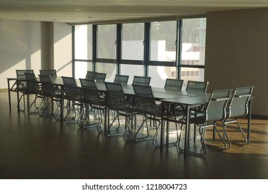 A contemporary conference / meeting room with steel and leather chair and a large glass table.