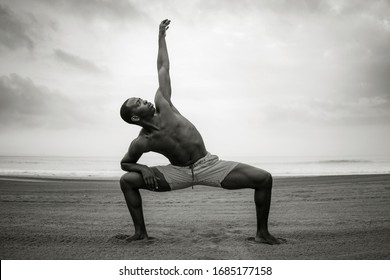 contemporary dance choreographer and dancer doing ballet beach workout - young attractive and athletic black African American man dancing outdoors doing beautiful dramatic performance