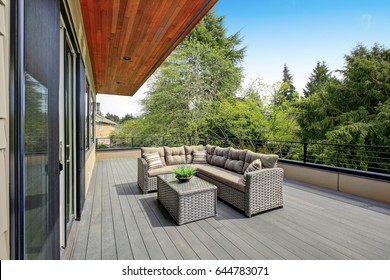 Contemporary deck features a modern wicker sectional accented with gray seat cushions facing a wicker coffee table. Northwest, USA