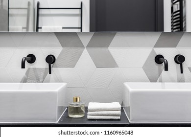 Contemporary designed bathroom with two washbasins with black faucets