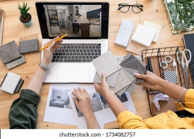 Contemporary designer pointing at home interior example on laptop display while consulting with colleague holding linoleum samples