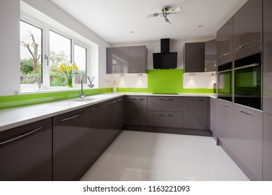 Contemporary fitted kitchen in striking lime green, grey and white colour scheme with built in appliances, white granite counter tops dual ovens and hob