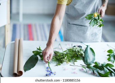 Contemporary florist taking iris flower from desk to put it into bunch of green leaves and yellow rose