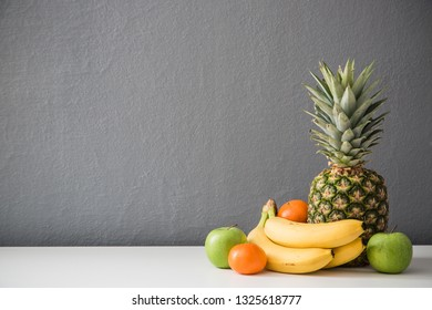 Contemporary fruit still life against gray wall