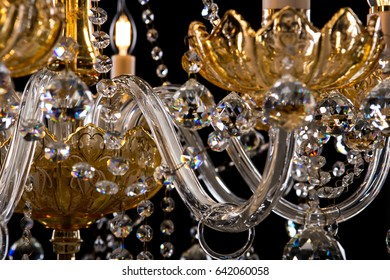 Contemporary gold chandelier isolated on black background. close-up . Crystal chandelier