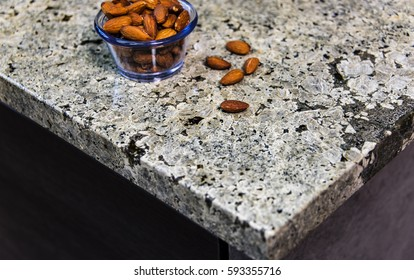Contemporary gray and white granite kitchen countertop with nuts on it.