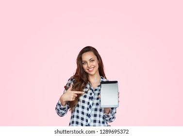 Contemporary happy casual woman with long hair showing modern touchpad on pink background