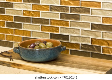 Contemporary home kitchen interior. Olives appetizers in glazed clay ceramic serving dish on countertop with glass mosaic tile backsplash