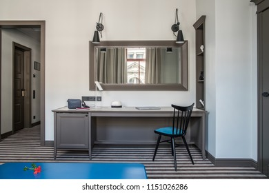 Contemporary hotel room with light walls and a striped floor. There is a blue table, wide table with a chair, different lamps, mirror on the wall, shelves with decorations, doors. Horizontal.