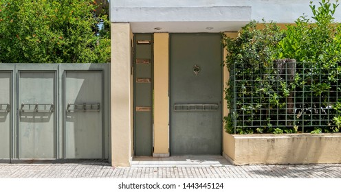 contemporary house entrance metalic grey door by the sidewalk, Athens Greece