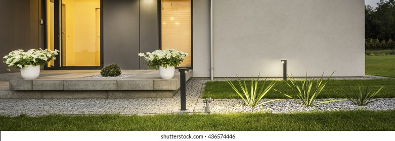 Contemporary house with garden and decorative outdoor lighting, external view, panorama