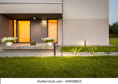 Contemporary house with garden and decorative outdoor lighting, external view