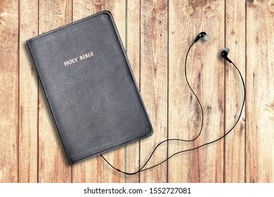 Contemporary image of a Bible with headphones.  Hearing the voice of God concept.
