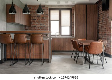 Contemporary interior design of light spacious dinning room including brown wooden furniture with bar stools at counter and soft comfortable chairs at table with cement effect in loft style