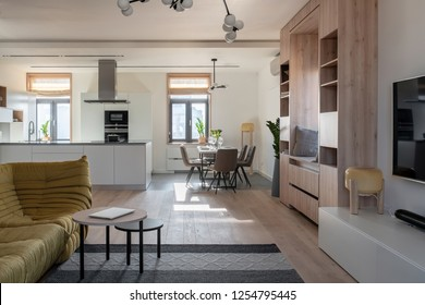 Contemporary interior with white walls, parquet with a carpet and tiles on the floor, kitchen zone. There is wooden bookcase, windows, table with dishes, chairs, green plants, sofa, TV, round tables.