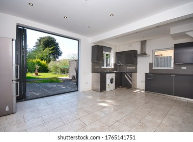 Contemporary Kitchen with bi folding aluminium doors leading to garden decking UK