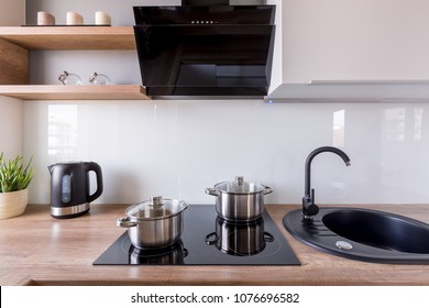 Contemporary kitchen with exhaust hood, new design black sink and induction hob
