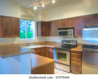 Contemporary kitchen with stainless steel appliances and granite backsplash