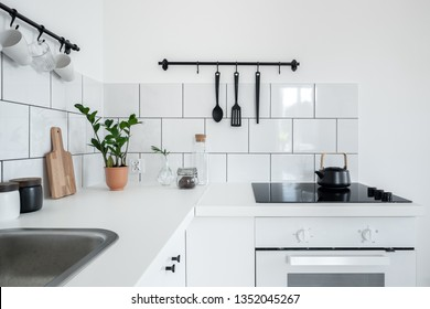 Contemporary kitchen with white wall tiles and functional black hangers
