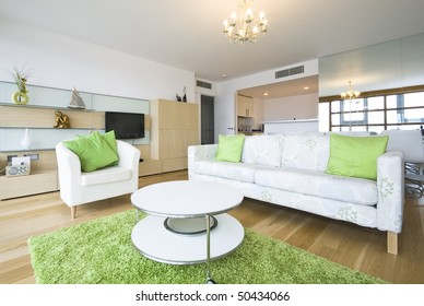 Contemporary living area with designer furniture, with green fragments and  floor to ceiling windows
