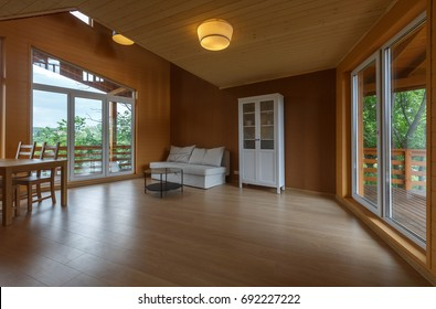 contemporary living room. minimalistic interior in wooden cottage with wooden floor and wooden ceiling. white cupboard. white sofa. laminate floor.