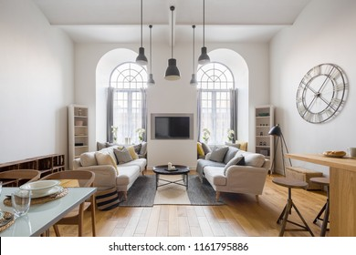 Contemporary living room with tv, two sofas and arch windows