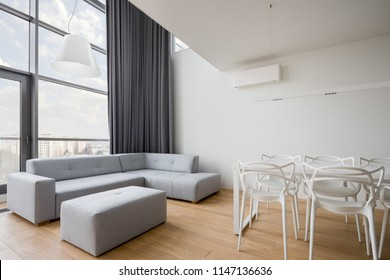 Contemporary living room with white table, gray sofa and window wall