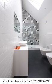 Contemporary loft bathroom with high ceiling, walk in shower, black vinyl floor and black and white monochrome porcelain wall tiles.
