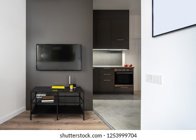 Contemporary luminous interior with white and gray walls and parquet, kitchen zone with tiled floor. There is a black stand with books and cups, TV, lockers, sink, drawers, oven and stove, door.