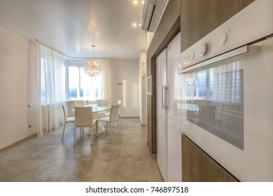 Contemporary luxury apartment for sale.  Open space kitchen and living room combined. White counter top, orange curtains, big panoramic windows, big white fridge, brown decorative wooden panels.