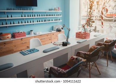 Contemporary manicure tools locating on long desk in beauty salon. Cozy chairs situating near it. Design concept