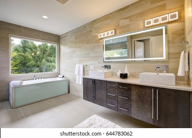Contemporary master bathroom features a dark vanity cabinet fitted with rectangular his and hers sink and modern wall mount faucets, also modern tub by the window. Northwest, USA