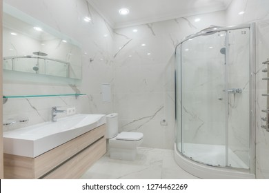 Contemporary master bathroom features a vanity cabinet fitted with rectangular sink and modern faucet under large mirror. Glass shower with rain shower head