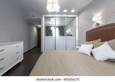 Contemporary modern bright bedroom with big closet and luxury bed in a luxury apartment downtown. white dresser.