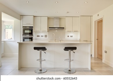 Contemporary modern cream colored luxury kitchen with fitted appliances and breakfast bar