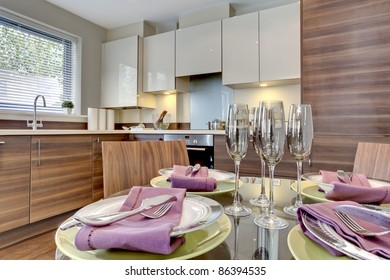Contemporary modern kitchen with table in the foreground dressed for dining with plates, bowls, serviettes, cutlery and wine glasses