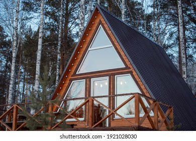 Contemporary new large country house standing in mixed forest in front of camera on background of pine trees and birches growing together