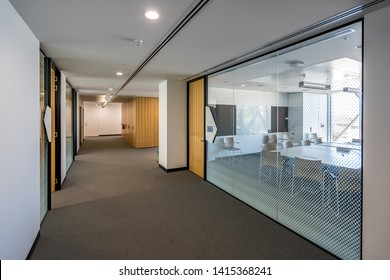 Contemporary office building corridor with meeting rooms on the side