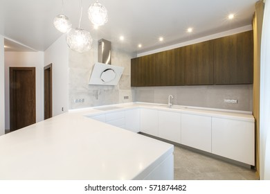 Contemporary open space kitchen in a luxury apartment. White counter with white furniture.