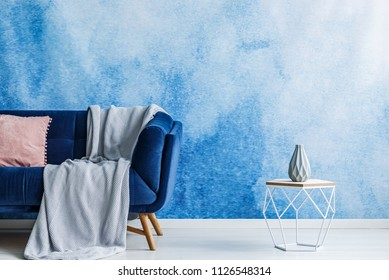 Contemporary openwork metal side table with vase next to a dark sofa with blanket and pillow standing against a blue and white ombre wall in a modern living room interior. Real photo.