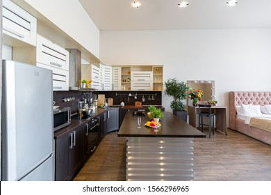 Contemporary ordinary design of spacious studio in soft warm colors. Simple furniture. Light large room with sunlight. Daytime. Tiled brown floor and white walls .
