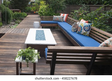 A contemporary outdoor conversation bench with pillows on a wooden deck.