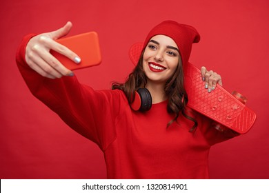 Contemporary pretty girl with red lips wearing stylish red clothes and posing with longboard while taking selfie