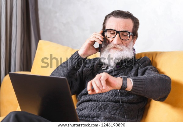 Contemporary senior bearded man in glasses and grey pullover chatting on the smartphone and watching time in his apple watch while sitting on the yellow sofa in the light living room, modern