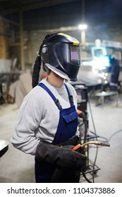 Contemporary shipbuilding engineer in protective workwear going to carry out welding work