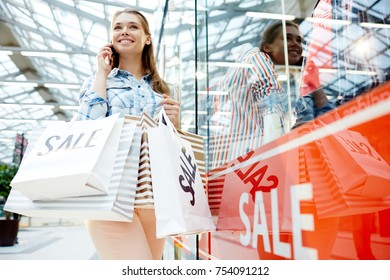 Contemporary shopper with paperbags talking on smartphone in large department store