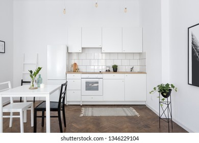 Contemporary, simple white kitchen interior with white dining table
