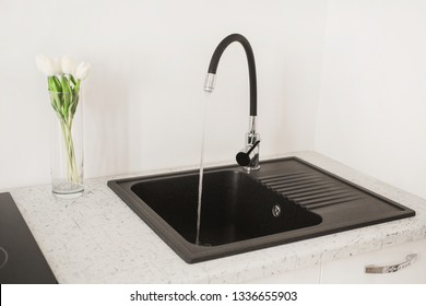 Contemporary sink with tap in the luxury kitchen. White luxury furniture. New black open faucet. Modern apartment. Water flow from the tap in the kitchen. Open faucet. Flowing water. Sink from stone