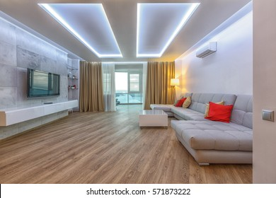 Contemporary spacious living room with hardwood floor, white ceiling, golden curtains, grey innovative coach, red decorative pillows. Sophisticated lightning.