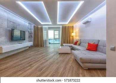 現代の広々としたリビングルームで、堅木の床、白い天井、金色のカーテン、グレーの革新的なコーチ、赤い飾りの枕。洗練された稲妻。